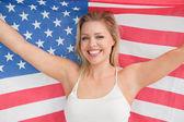 Lächelnde frau hissen der amerikanischen flagge — Stockfoto