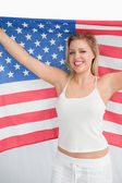 Happy blonde woman holding the Old Glory flag — Stock Photo