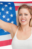 Smiling woman holding the Old Glory flag — Stock Photo