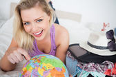 Beautiful woman with a suitcase pointing on a globe — Stock Photo