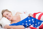Laughing blonde woman with a US flag — Stock Photo