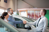 Salesman smiling while shaking the hand of a customer — Stock Photo