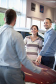 Couple smiling and chatting with a salesman — Stock Photo