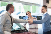 Car dealer shaking hand with a smiling man — Stock Photo