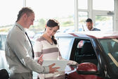 Smiling woman chatting with a car dealer — Stock Photo