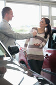 Smiling woman receiving keys from a salesman — Stock Photo