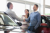 Man shaking a car dealer hand — Stock Photo
