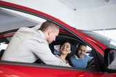 Couple in a car listening to a salesman — Stock Photo