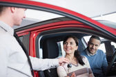 Couple sitting in a car receiving key from a car dealer — Stock Photo