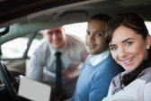 Smiling couple in a new car — Stock Photo