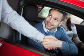Man shaking the hand of a car dealer — Stock Photo