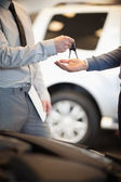 Salesman handing keys to a customer — Stock Photo