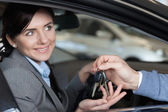 Smiling woman receiving keys from a man — Stock Photo