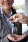 Hand holding keys over the hand of a woman — Stock Photo