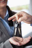 Woman smiling while receiving keys — Stock Photo