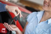 Smiling woman receiving keys from somebody — Stock Photo