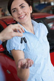 Woman smiles while receiving a car key — Stock Photo