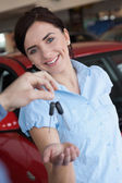 Woman smiling and receiving car keys — Stock Photo