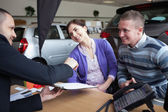 Couple chatting with a car salesman — Stock Photo