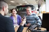 Pareja sonriendo mientras hablaba con un vendedor — Foto de Stock