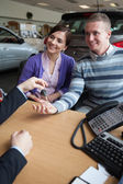 Happy couple receiving keys from a salesman — Stock Photo