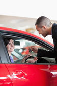 Smiling woman receiving car keys — Stock Photo