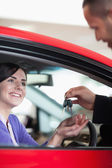 Woman smiling while receiving car keys — Stock Photo