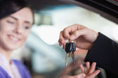 Woman in a car receiving keys — Stock Photo