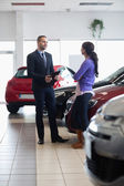 Salesman and a woman talking next to a car — Stock Photo