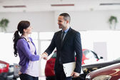 Smiling salesman shaking the hand of a woman — Stock Photo
