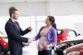 Salesman shaking the hand of a woman and giving her car keys — Foto Stock
