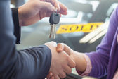 Person shaking hands in front of a sold car — Stock Photo