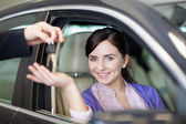 Lachende vrouw glimlacht als ze zit in een auto — Stockfoto