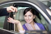 Lächelnde frau lächelt als she sitzt in einem auto — Stockfoto