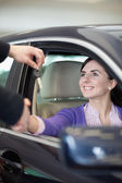 Woman smiling in a car while shaking hand — Stock Photo