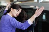 Woman hugging a grey car — Zdjęcie stockowe
