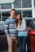 Couple holding tight while standing next to a car — Stock Photo