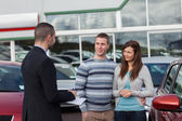 Salesman talking to a couple — Stock Photo