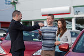 Salesman giving car keys to a couple — Stock Photo