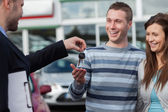 Couple receiving car keys by a dealer — Stok fotoğraf