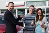 Dealer shaking hand of a man while giving him car keys — Foto de Stock