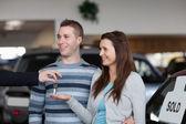 Verkäufer geben autoschlüssel mit einer frau — Stockfoto