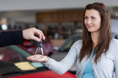 Woman receiving car keys in his hand — Stock Photo