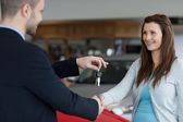 Man giving car keys while shaking hand of a woman — Stock Photo