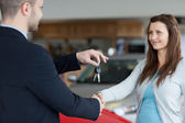 Salesman giving car keys while shaking hand of a woman — Stock Photo
