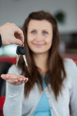 Happy brunette receiving car keys — Stock Photo