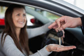 Happy woman receiving car keys — Stock Photo