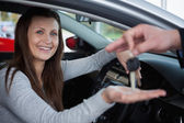 Happy client receiving car keys — Stock Photo