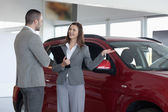 Businesswoman showing a car to a client — Stock Photo