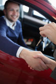 Customer receiving car keys while shaking hand — Stock Photo